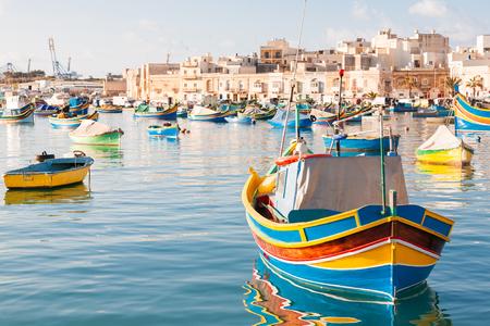 Bunte typische Boote - Mittelmeer traditionellen Fischerdorf im Südosten von Malta. Am frühen Wintermorgen in Marsaxlokk, Malta. Standard-Bild