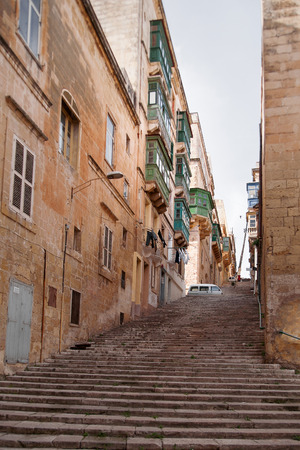 carved stone: Ancient staircase street in Valletta, Malta. Narrow street with old fashioned balcony, carved stone walls and arches. Stock Photo