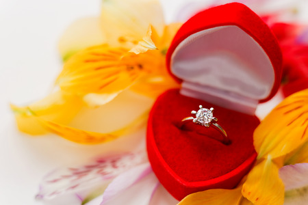 Engagement diamond ring in red gift box on pile of flower petals. Symbol of love and marriage.