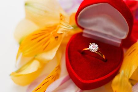 anillo de compromiso: anillo de diamantes de compromiso en rectángulo de regalo rojo en la pila de pétalos de flores. Símbolo del amor y el matrimonio.