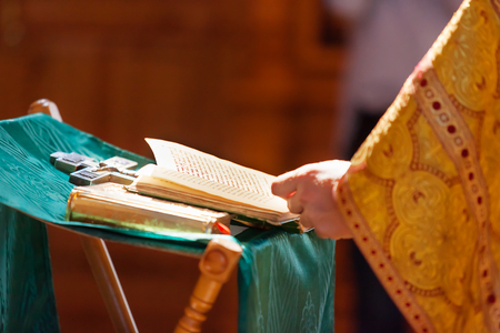 vestment: Prayer book in the hands of the priest. Ceremony in the Orthodox Christian Church. Russia. Selective focus. Stock Photo