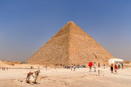 Tourists are walking near the Great Pyramid of Giza.