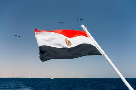 flapping: The national flag of Egypt is flapping in the wind above the Red sea. Stock Photo