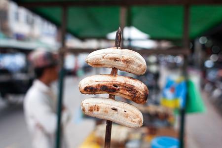 platanos fritos: postre tradicional en Asia - los plátanos fritos en el palo. Fruta sabrosa está en venta en la pequeña tienda de la calle. Bangkok, Tailandia.
