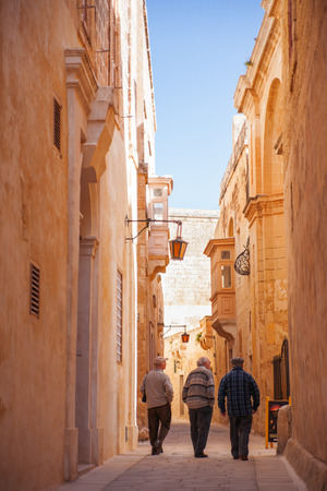 mediterranian houses: Three old man are walking down ancient narrow street in Mdina, Malta.