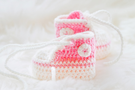 bootees: Little baby shoes. Hand knitted first sneakers for newborn  girl. Crochet handmade pink bootees on fluffy white background. Stock Photo