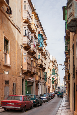 carved stone: Ancient street in Valletta, Malta. Narrow street with old fashioned balcony, carved stone walls and arches.