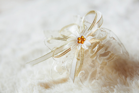 garter: Brides garter. Brides traditional symbolic accessory. White lace with yellow flower.
