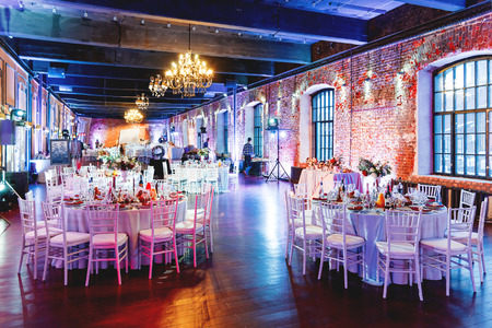Celebration hall with tables set for banquet in loft. Vintage room with brick walls without plaster or wallpapers. Table decorated with candles, fabric and flowers. Editorial