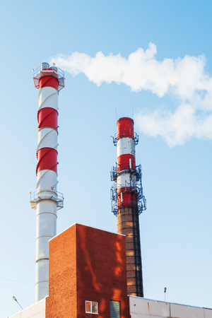 boiler house: Boiler house chimney. Steam against the clear blue sky. Industrial zone of the city.
