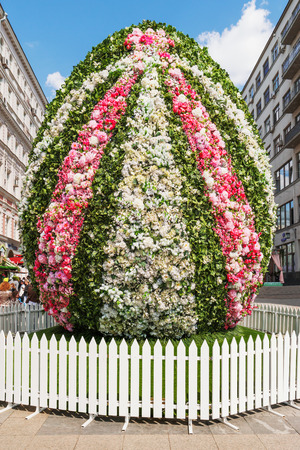 giant easter egg: MOSCOW, RUSSIA - April 30, 2016. Giant Easter egg made of flowers. Street festival Moscow Spring in historical center of Moscow city. Flower decoration of colorful easter fair. People walking on sunny day. Editorial