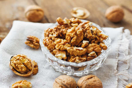 homespun: Glass bowl with walnuts on rustic homespun napkin. Healthy snack on old wooden background.