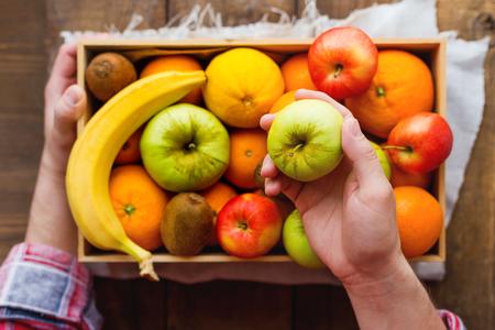 Man in tartan plaid shirt holds a box full of fresh fruits and a green apple. Fruit harvest - apples, oranges, lemon, kiwi, banana. Rustic wooden table.