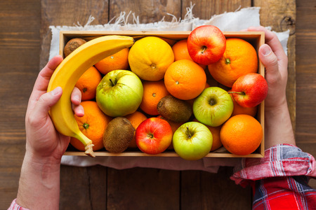 apples and oranges: Man in tartan plaid shirt holds a box full of fresh fruits and a banana. Fruit harvest - apples, oranges, lemon, kiwi, banana. Rustic wooden table.