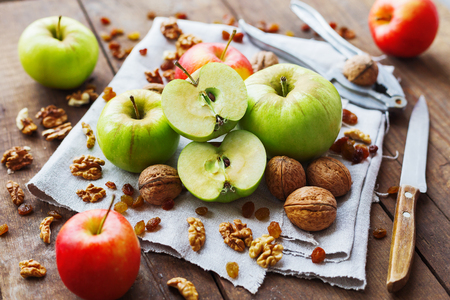 healthy snack: Healthy snack background - fruits and nuts. Green and red apples, raisins and walnuts on rustic wooden background.