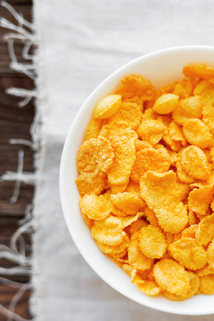 homespun: Tasty corn flakes in bowl. Rustic wooden background with homespun napkin. Healthy crispy breakfast snack. Top view, flat lay. Stock Photo