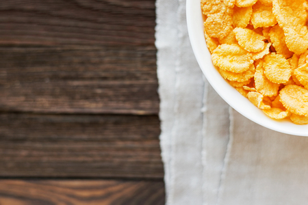 homespun: Tasty corn flakes in bowl on homespun napkin. Rustic wooden background. Healthy crispy breakfast snack. Place for text. Top view, flat lay.