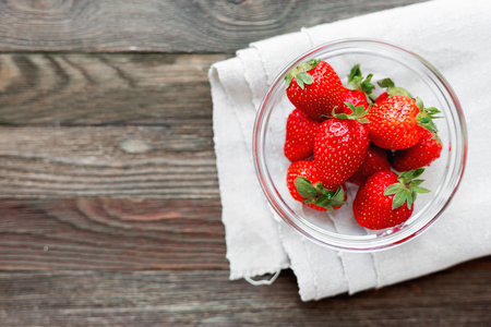 homespun: Fresh juicy strawberries in glass bowl. Rustic background with homespun napkin. Top view. Place for text.