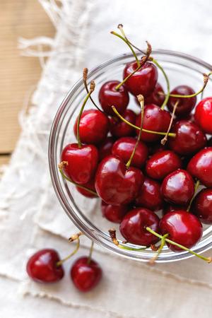 homespun: Fresh juicy sweet cherries in glass bowl. Rustic background with homespun napkin.