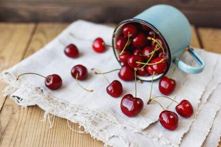 homespun: Fresh juicy sweet cherries  in old rusty mug. Rustic background with homespun napkin.