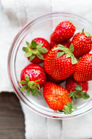 homespun: Fresh juicy strawberries in glass bowl. Rustic background with homespun napkin. Top view. Stock Photo