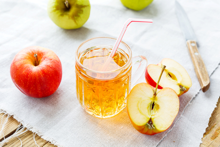 homespun: Rustic background with apples and apple juice in glass on homespun napkin. Stock Photo