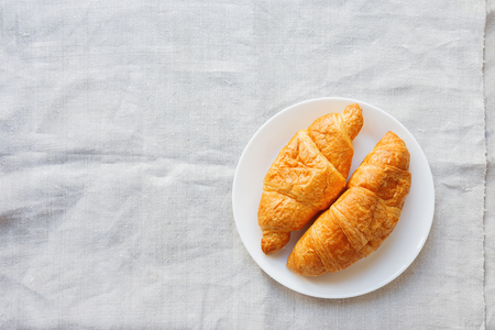 homespun: Continental breakfast background - pair of croissants on homespun napkin. Rustic wooden background with place for text. Top view. Stock Photo