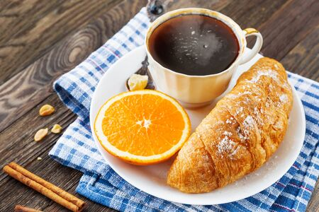 Continental breakfast - cup of hot coffee, croissant and orange. Tasty food on plaid blue napkin, rustic wooden background.