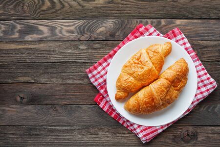 Continental breakfast background - pair of croissants on plaid red napkin. Rustic wooden background with place for text. Top view.