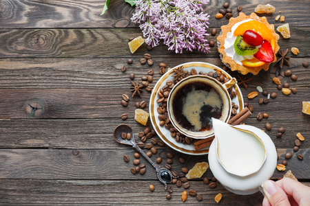 Rustic wooden background with cup of coffee, milk, fruit tart and lilac flowers. White vintage dinnerware and spoon. Breakfast at summer morning. Top view, place for text.