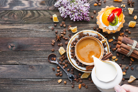 morning coffee: Rustic wooden background with cup of coffee, milk, fruit tart and lilac flowers. White vintage dinnerware and spoon. Breakfast at summer morning. Top view, place for text.