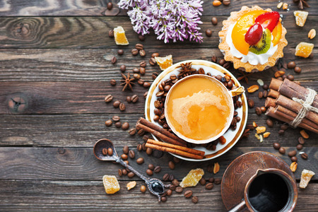 morning breakfast: Rustic wooden background with cup and cezve of coffee, fruit tart and lilac flowers. White vintage dinnerware and spoon. Breakfast at summer morning. Top view, place for text.