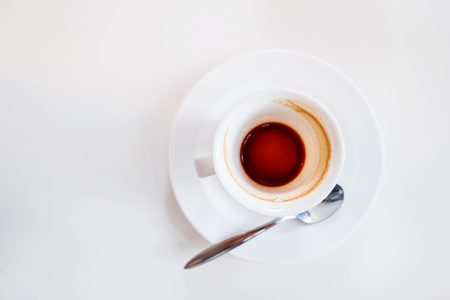 Empty coffee cup on white background. End of coffee break. Coffee grinds in white mug.