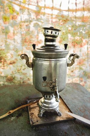 Brass samovar, tin-plated. Vintage Russian device to heat water by firewood for beverages. Old fashioned, antique metal kettle. Rustic background. Stock Photo