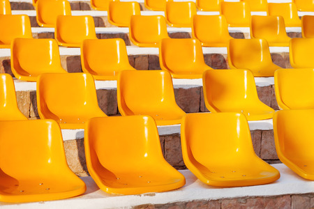 onlooker: Stone steps with yellow plastic seats. Empty stools without people.