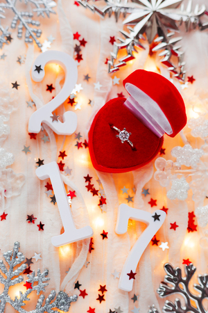 ring light: Christmas and New Year 2017  background with engagement ring, light bulbs and decorations. Symbol of love and marriage in 2017 year.