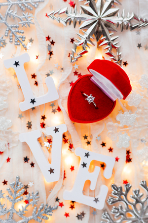 ring light: Christmas, New Year and Valentines Day background with engagement ring, light bulbs and decorations. Symbol of love and marriage.