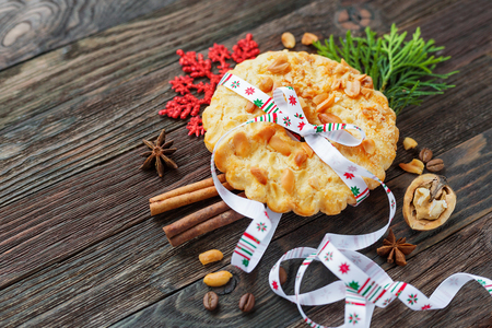 Christmas and New Year 2017 background with peanut tart and decorations - snowflake, ribbon, spices. Place for text. Stock Photo
