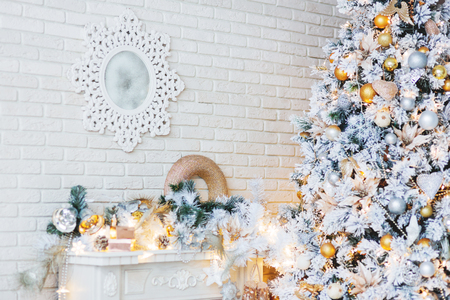 mantelpiece: Christmas and New Year Eve Tree. Holiday winter background. Interior details - mirror-snowflake, mantelpiece with garland of light bulbs. Stock Photo