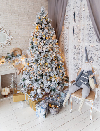 mantelpiece: Christmas and New Year Eve Tree. Holiday winter background. Interior details - mirror-snowflake, mantelpiece with garland of light bulbs, many presents and elf with gifts. Stock Photo