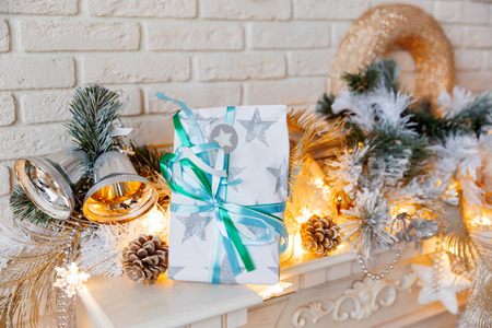 mantelpiece: Christmas and New Year decorations on mantelpiece. Holiday winter background with wrapped present. Gift with paper bow.