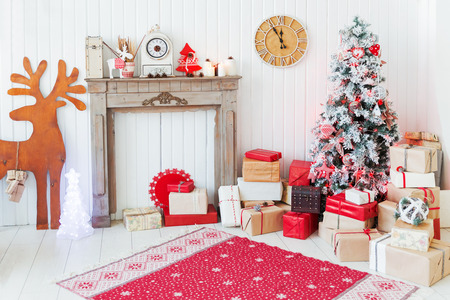 mantelpiece: Christmas and New Year details of home interior - wooden deer, mantelpiece with candles, Eve tree and presents. Stock Photo