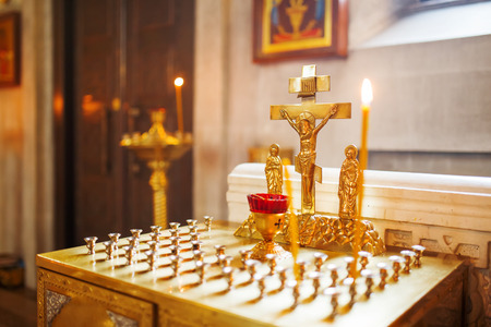 Golden candleholder in Orthodox church. Symbolic Orthodox gold cross with the crucifixion of Jesus. Stock Photo