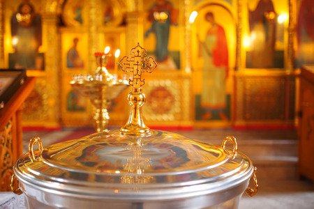 ordenanza: The font for the baptism of children in the Orthodox Church. Symbolic Orthodox gold cross on the cover font.