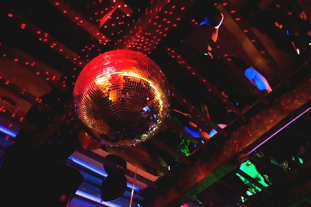 discoteque: Shining bright red mirror disco ball. Interesting device for discotheque, dancing party with music in night club.