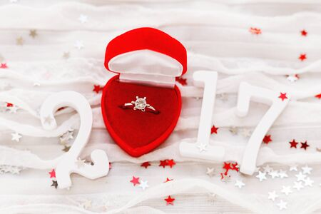 New Year 2017 on white fabric background with engagement diamond ring in red gift box. Good for Valentines day and Happy New Year cards. top view, flat lay. Place for text. Banco de Imagens