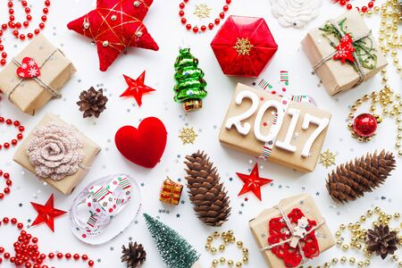Christmas and New Year 2017 background with decorations. Gifts in craft paper, pine cones, red hearts and confetti. Flay lay, top view.