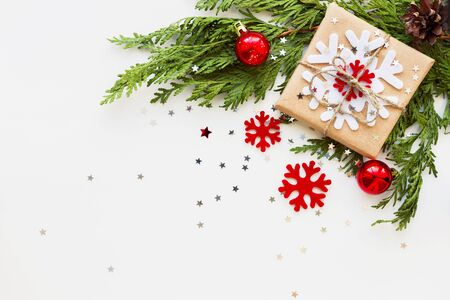 Christmas and New Year background with thuja branch, decorations and present wrapped in craft paper with snowflakes. Flat lay, top view. Place for text. Stock Photo
