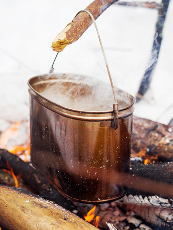 vapore acqueo: Cooking soup on a fire pot. Winter camping in forest.