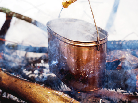Cooking soup on a fire pot. Winter camping in forest.